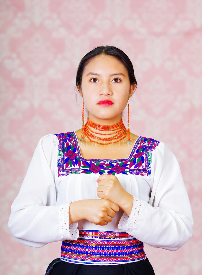 Young woman wearing traditional andean dress, facing camera doing sign language word for employee stock photography