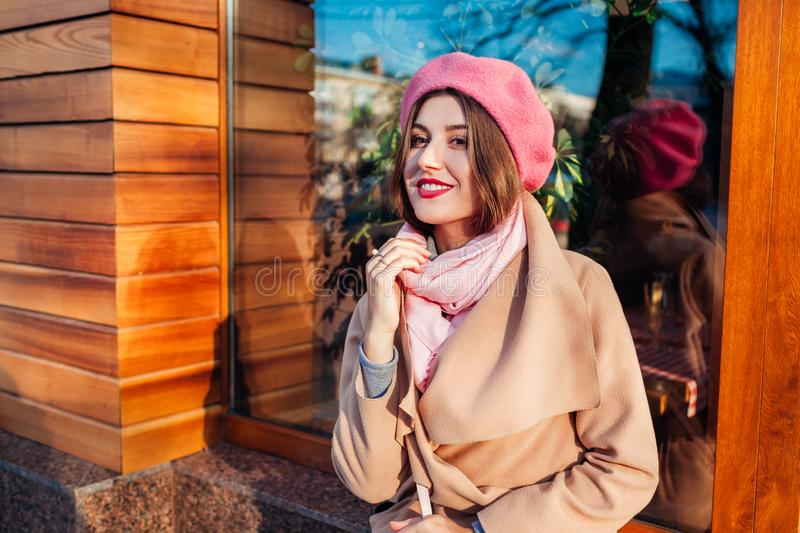 Young woman wearing trendy coat and beret outdoors. Spring female clothes and accessories. Fashion stock image