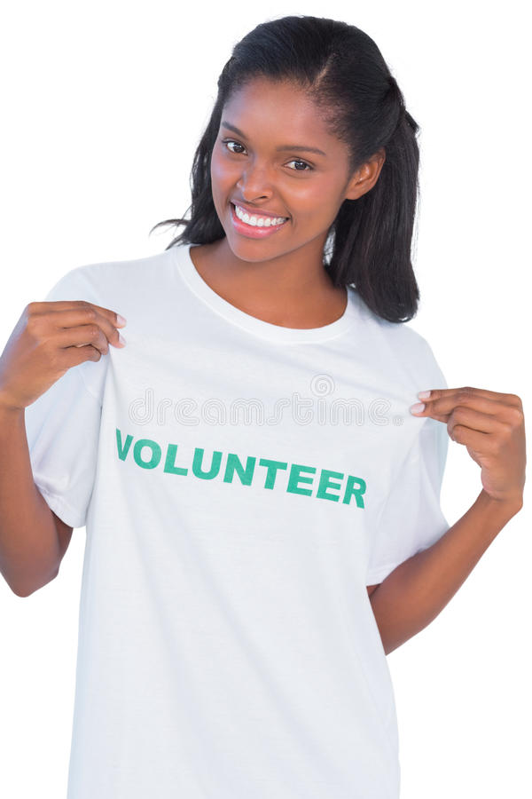 Young woman wearing volunteer tshirt and pointing to it royalty free stock image