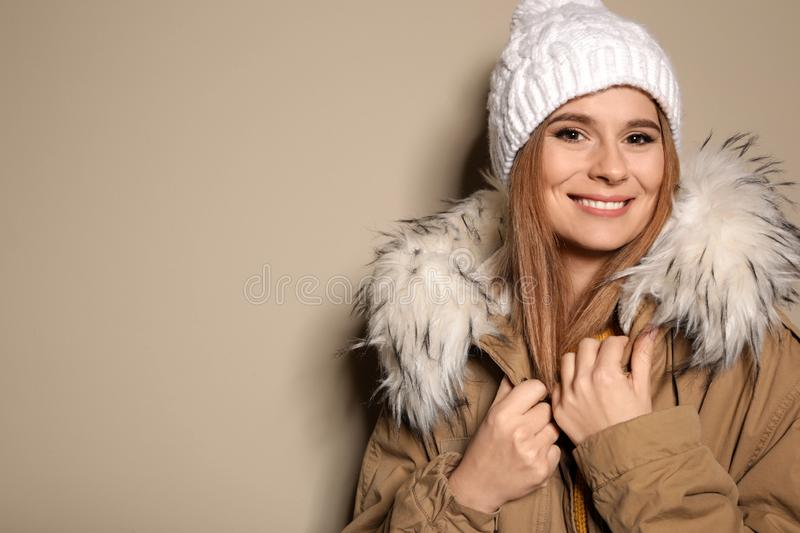 Young woman wearing warm clothes on color background, space for text. Ready for winter. Vacation royalty free stock photography