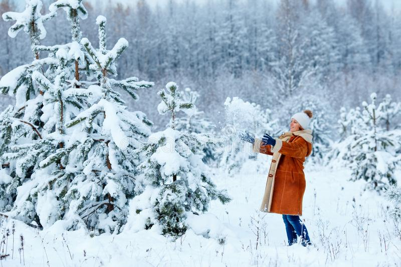 Young woman wearing warm clothes having fun on winter forest stock images