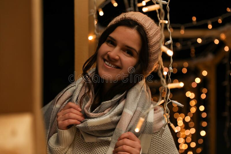 Young woman wearing warm sweater, hat and scarf at night. Winter season. Young woman wearing warm sweater, hat and scarf  outdoors at night. Winter season stock photo