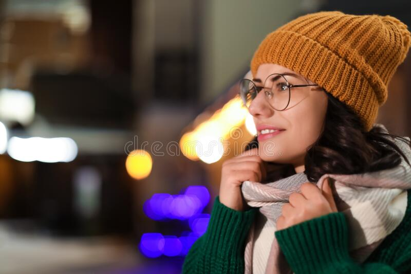 Young woman wearing warm sweater, hat and scarf  at night. Winter season. Young woman wearing warm sweater, hat and scarf  outdoors at night. Winter season royalty free stock photography