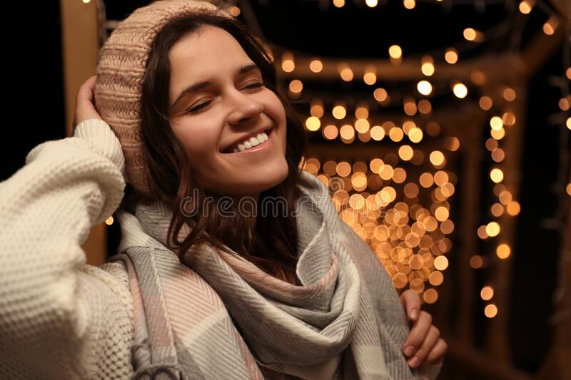 Young woman wearing warm sweater, hat and scarf  outdoors at night. Winter season. Young woman wearing warm sweater, hat and scarf  outdoors at night stock photos