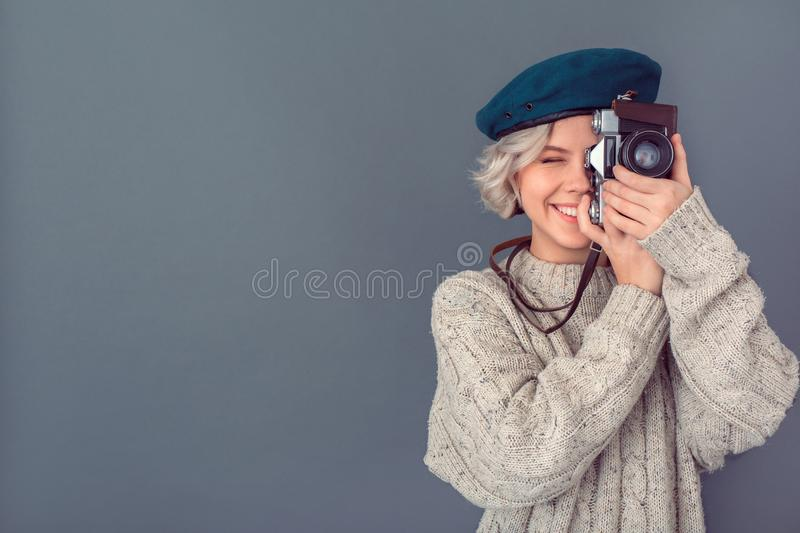 Young woman in a woolen sweater isolated on grey wall winter concept taking photos joyful royalty free stock image