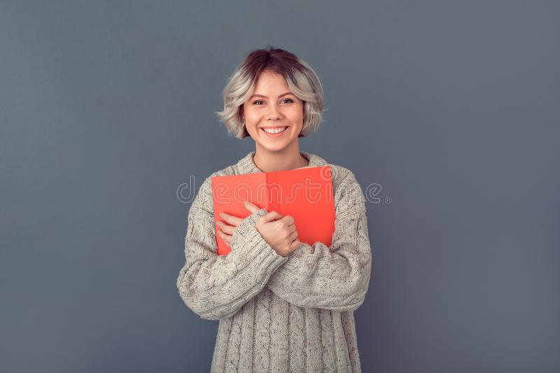 Young woman in a woolen sweater isolated on grey wall winter concept novel book stock image