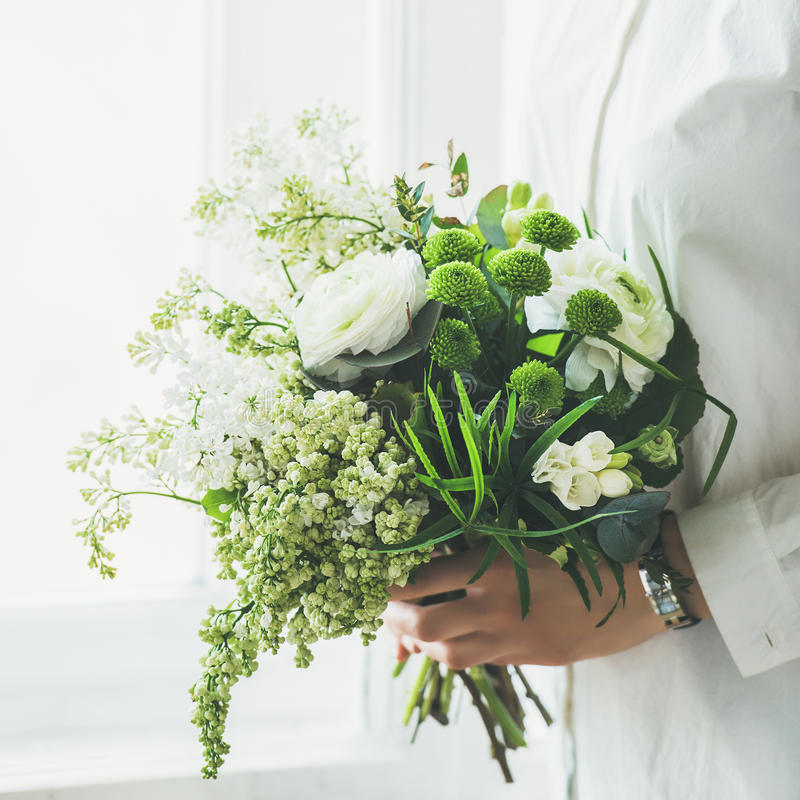 Young woman wearing white clothes holding flowers bouquet. Wedding concept. Young woman wearing white clothes holding white flowers bouquet composed of stock photos