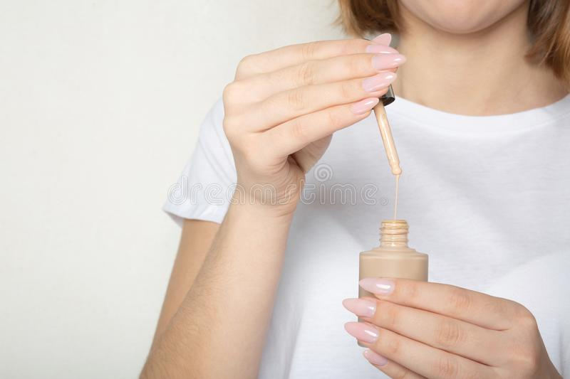 Young woman wearing white t shirt holding liquid foundation with pipette. Empty space stock photography