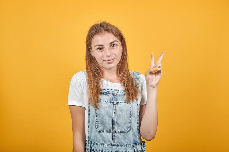 Young woman wearing white t-shirt, over orange background shows emotions royalty free stock images