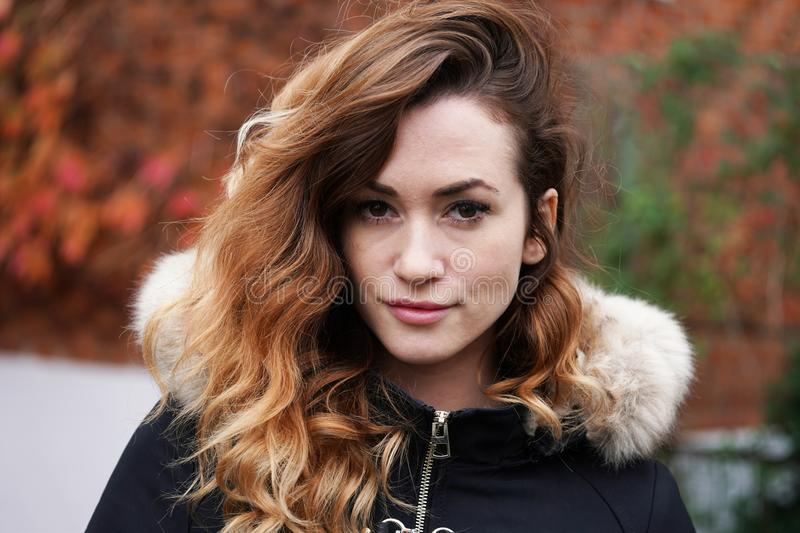 Young woman wearing winter coat. Portrait of a young woman wearing winter coat outdoors royalty free stock photography
