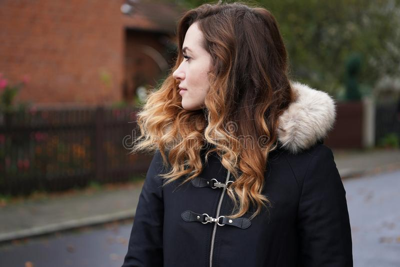 Young woman wearing winter coat on suburban street. In Germany stock photography