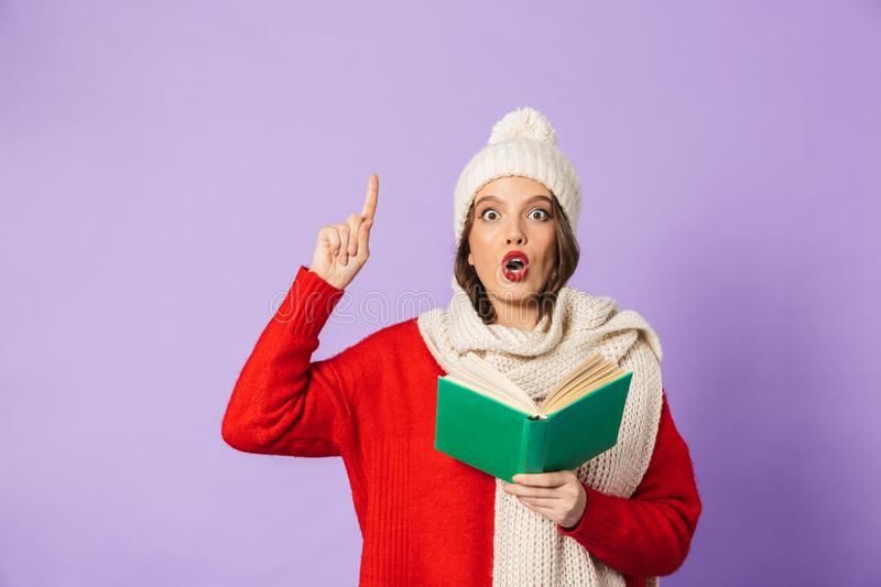 Young woman wearing winter hat isolated over purple background reading book. Portrait of an excited shocked young woman wearing winter hat isolated over purple royalty free stock images