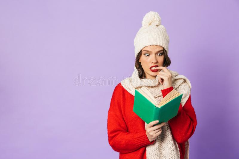 Young woman wearing winter hat isolated over purple background reading book. Portrait of thinking nervous young woman wearing winter hat isolated over purple stock photography