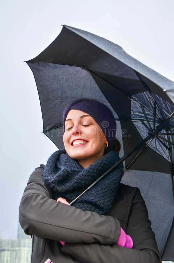 Young woman wearing winter jacket and gear holds a black umbrella, smiling, with eyes closed.  royalty free stock photos