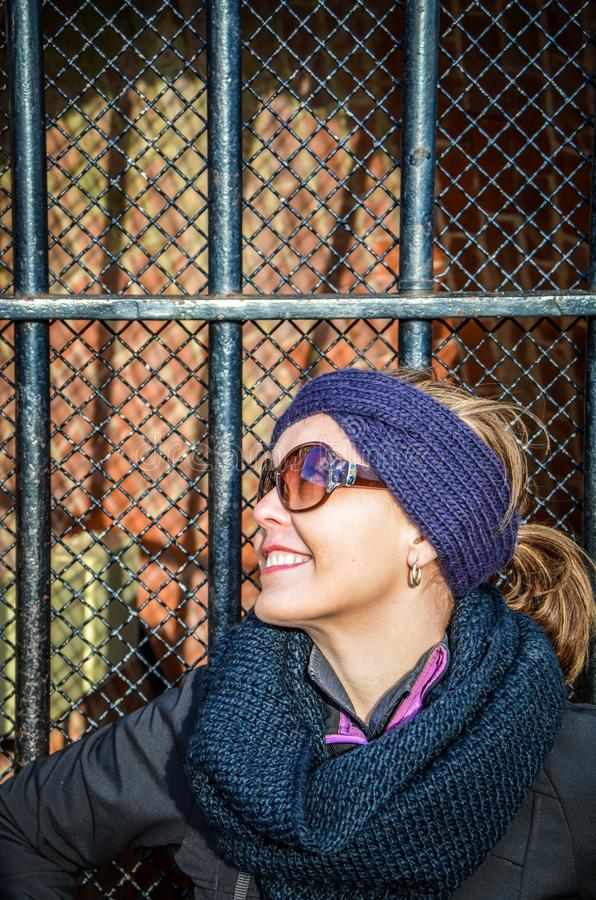 Young woman wearing winter jacket and gear poses against an urban gate fence in the sunlight. Wearing sunglasses royalty free stock image