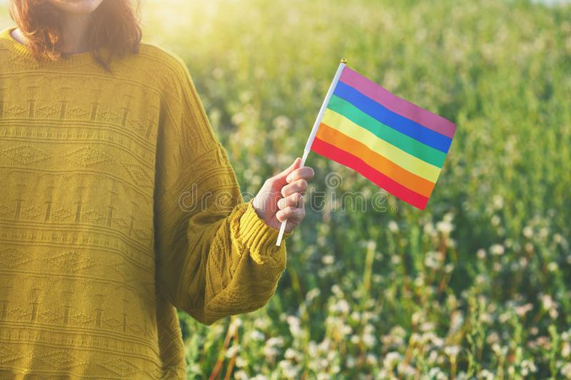 Woman wearing yellow sweater holding lgbt rainbow flag outside, same sex couples, freedom, love, equal rights concept, copy space royalty free stock image