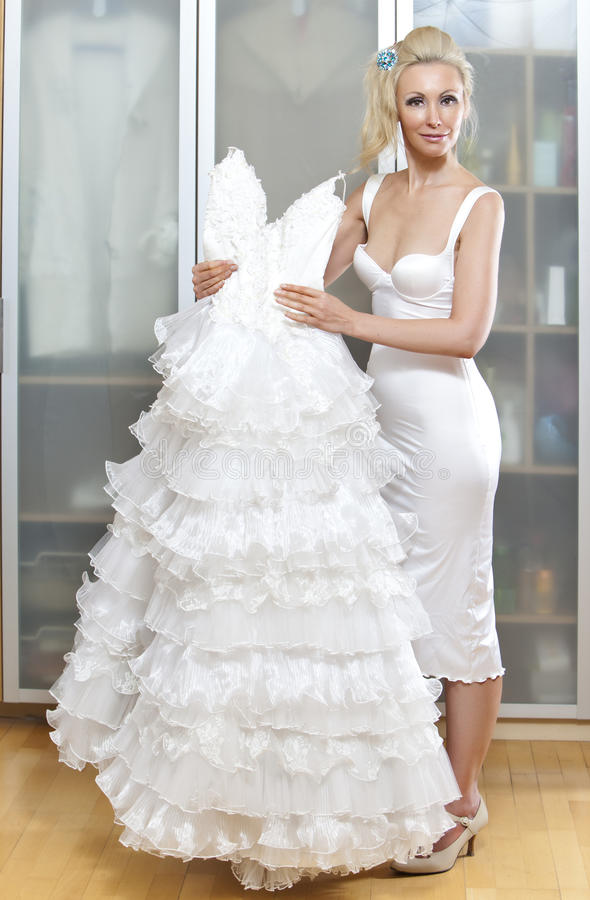 The young woman with a wedding dress in hands dreams about wedding stock image
