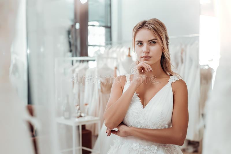 Young woman in a wedding dress looking thoughtful. Almost decided. Young pretty woman in a wedding dress standing in the middle of a wedding salon and looking stock image