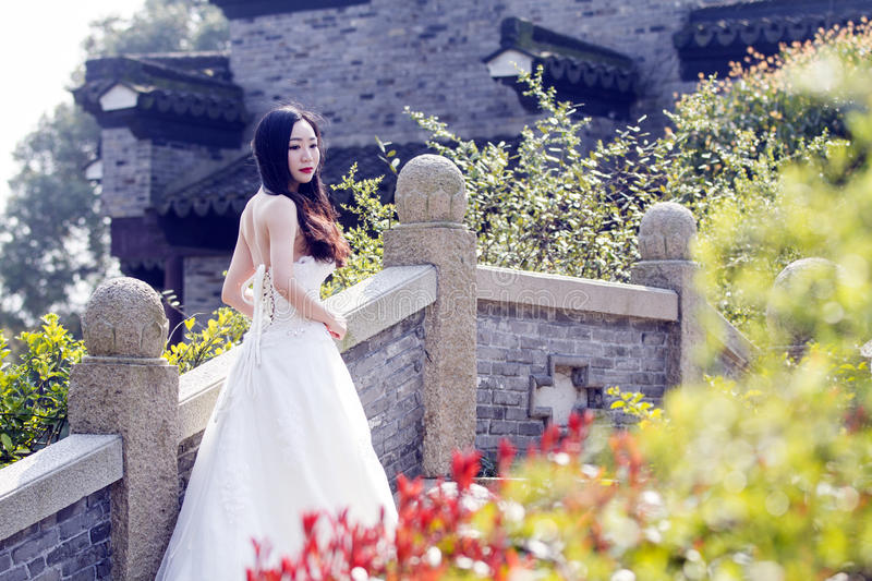 A young woman wedding photo/portrait stand on a ancient old bridge stock images