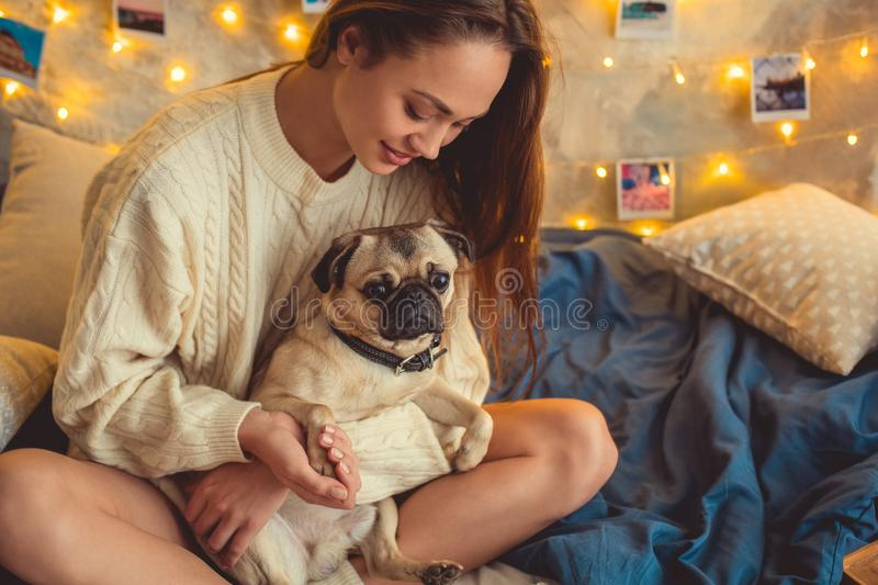 Young woman weekend at home decorated bedroom holding paw of dog royalty free stock images