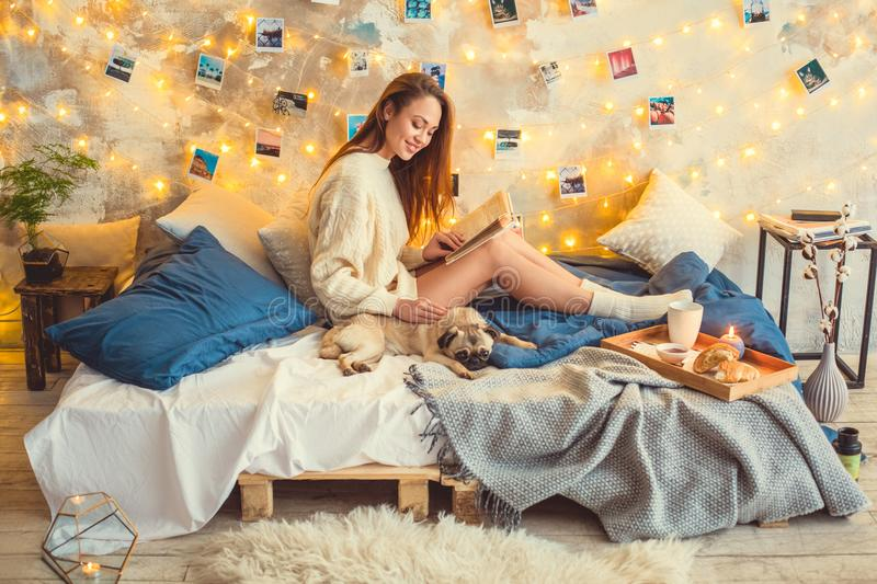 Young woman weekend at home decorated bedroom stroking dog reading book stock images