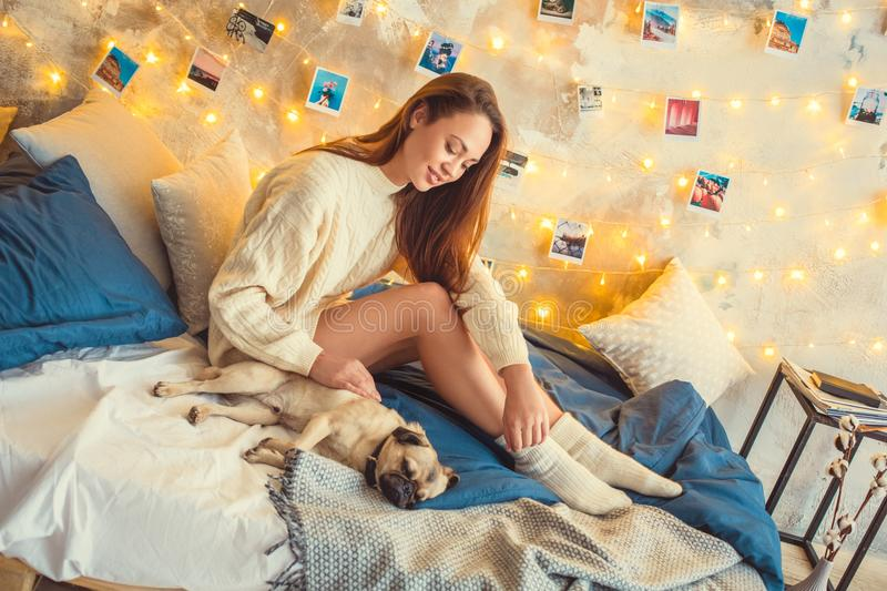 Young woman weekend at home decorated bedroom touching dog stock photos