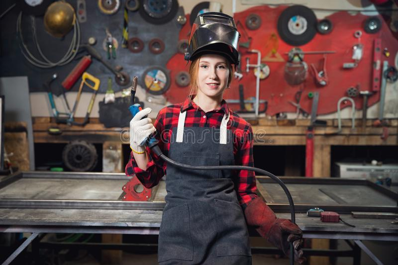 Young woman welder smiles and holds protective mask in hand on background industrial workplace or garage. Concept small royalty free stock photos