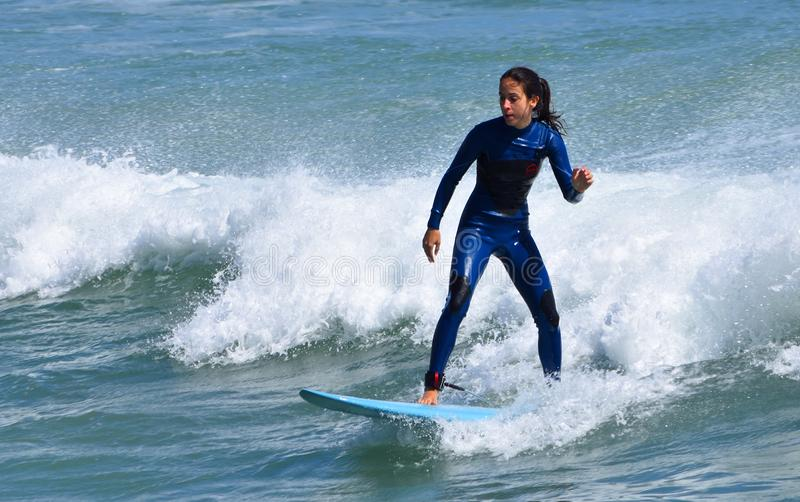 Young woman in wet suit on surf board riding wave. royalty free stock photography