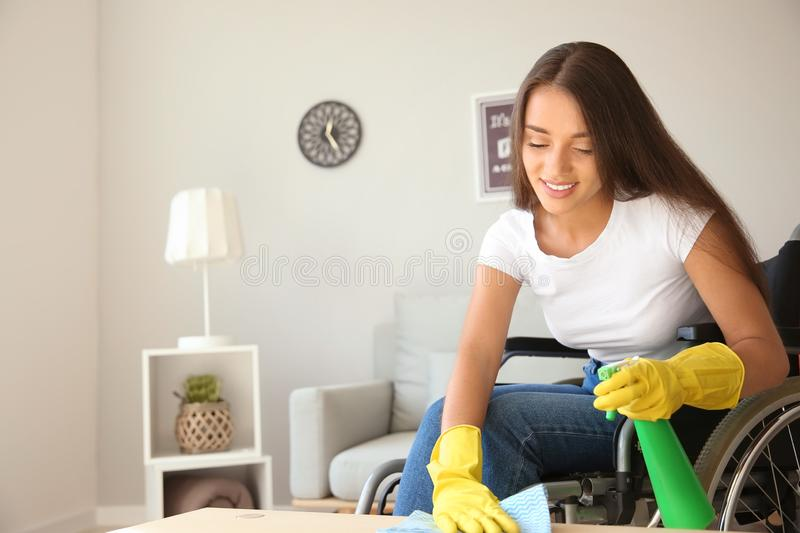 Young woman in wheelchair cleaning table at home stock photography