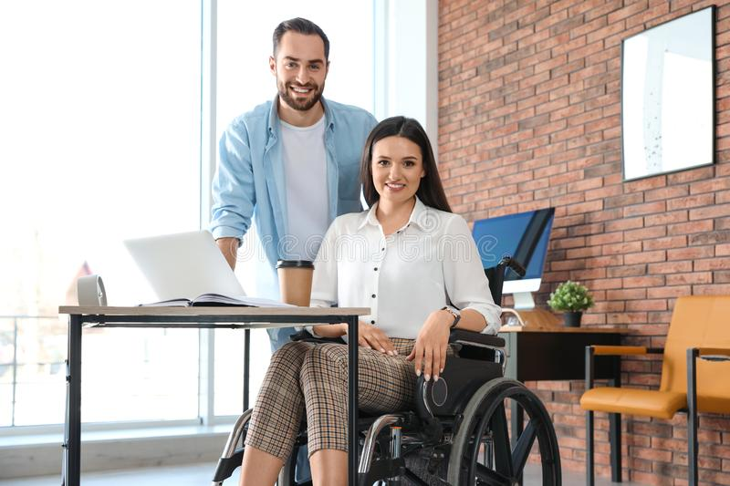 Young woman in wheelchair with colleagues. Young women in wheelchair with colleague at workplace royalty free stock photography