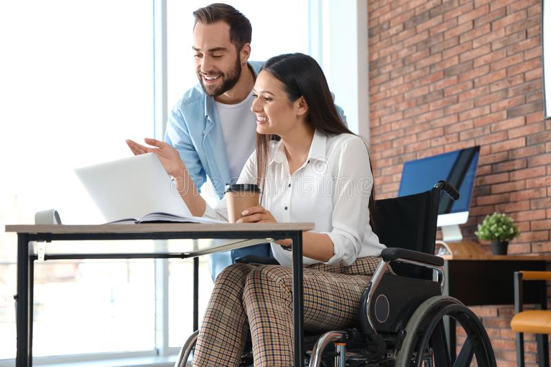 Young woman in wheelchair with colleague stock images
