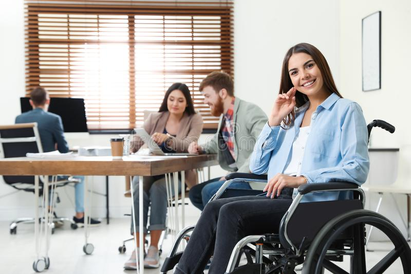 Young woman in wheelchair with colleagues stock photos
