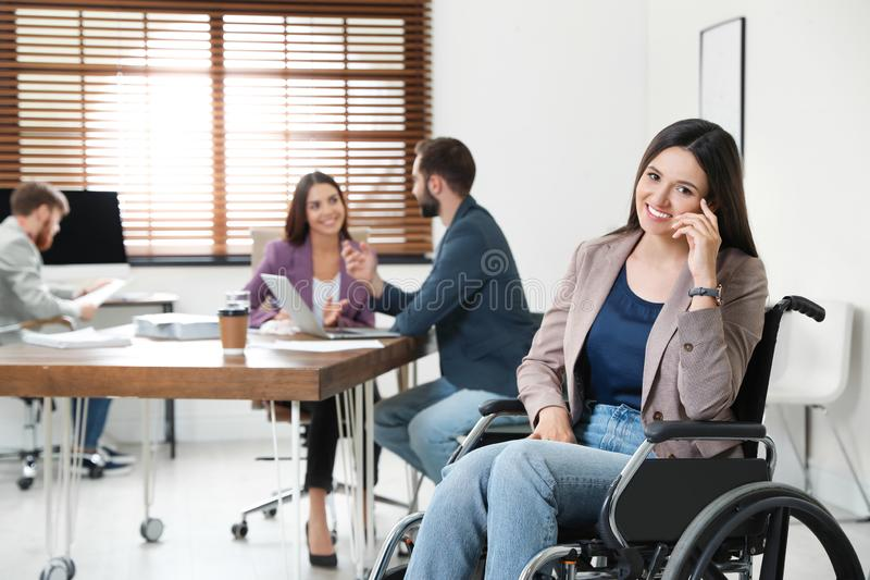 Young woman in wheelchair with colleagues stock photo