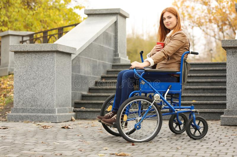 Young woman in wheelchair with cup of coffee royalty free stock photography