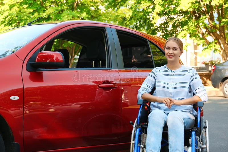 Young woman in wheelchair near car royalty free stock photo