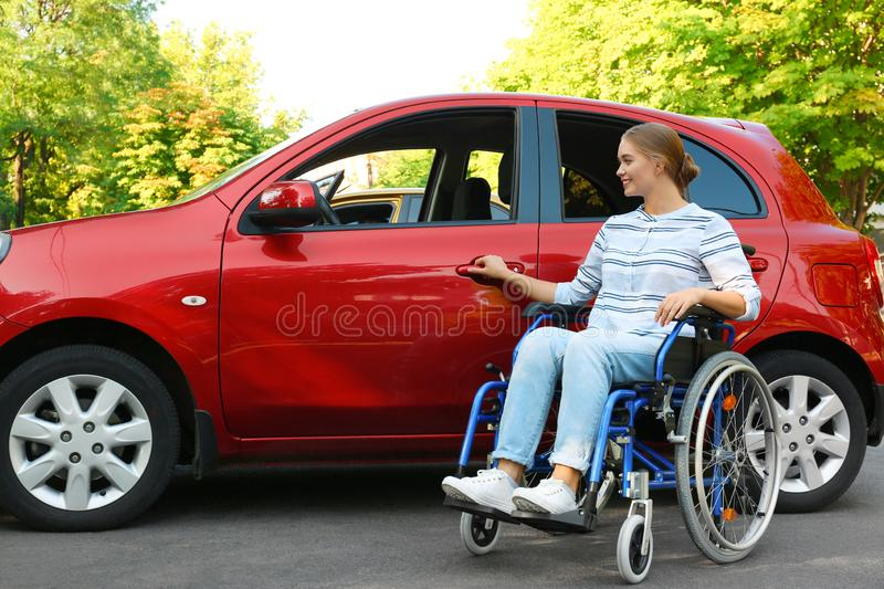 Young woman in wheelchair opening  of car outdoors stock photography