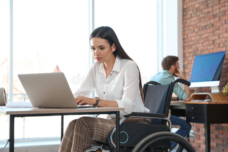 Young woman in wheelchair using laptop stock photography