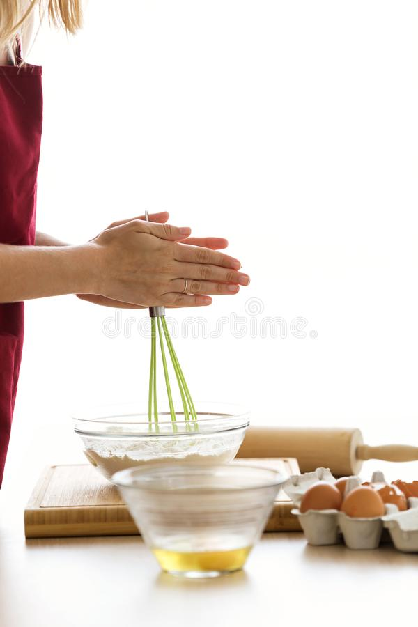 Young woman whisking eggs in glass bowl on kitchen table at home. stock images