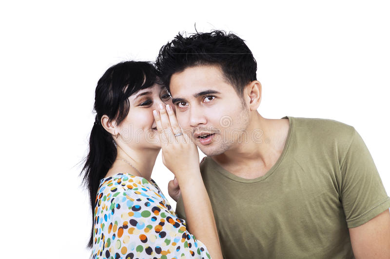 Young woman whispering a secret news stock image