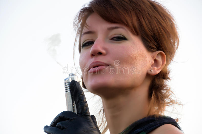 Young woman on white background holding a gun with a smoking gun.  stock photo