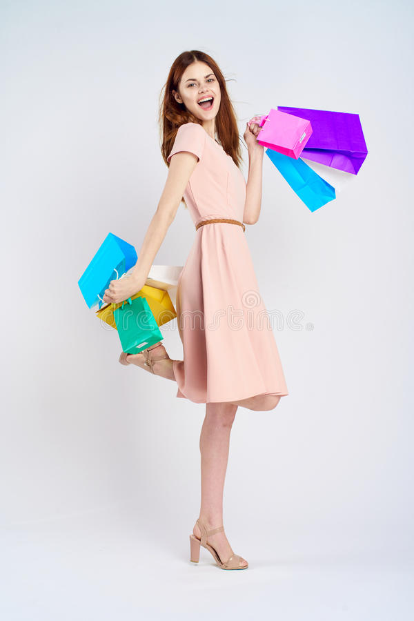 Young woman on a white background holds a lot of packages, shopping, full-length, joy, shopaholic royalty free stock photos