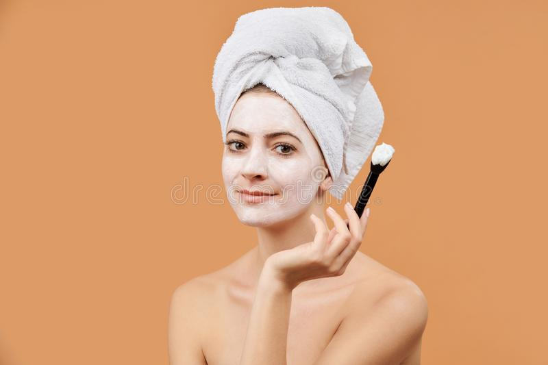 Young woman with white bath towel in her hair holding brush, applying face mask. Wellness and Spa concept on beige. stock image