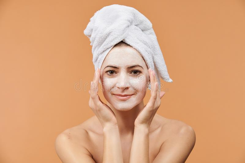 Young woman with white bath towel in her hair and mouisturizing face mask. Wellness and Spa concept on beige background. stock photo