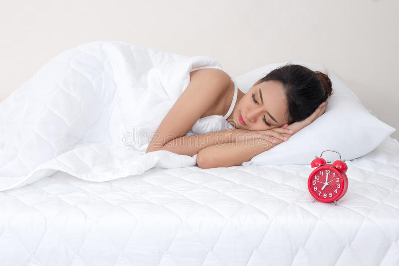 Young woman on white bed yawn awakening tired holding alarm clock. Lazily don`t want to wake up stock images