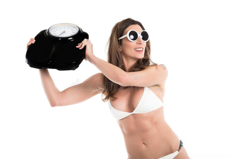 Young woman in white bikini furious hurl weight scale . Fit and healthy concept. Isolated over white background.  royalty free stock photo