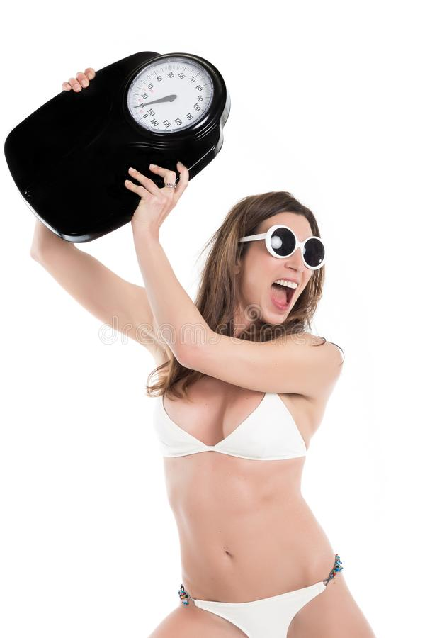 Young woman in white bikini furious hurl weight scale . Fit and healthy concept. Isolated over white background.  royalty free stock images