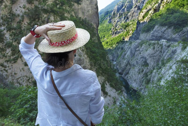 A young woman in a straw hat enjoying the view of a mountain river flowing down the stone gorge stock image