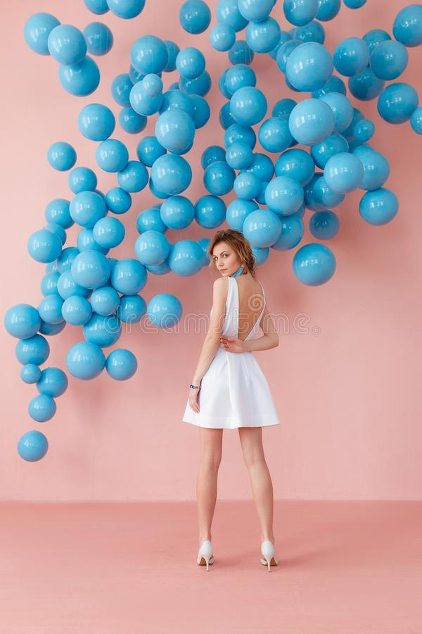 Young woman in white cocktail dress standing back to camera on pink wall background with blue bubbles hanging. Dreaming. Concept stock image