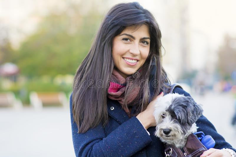 Young woman with white dog in a carry bag. Young woman with white dog in carry bag in the park stock image