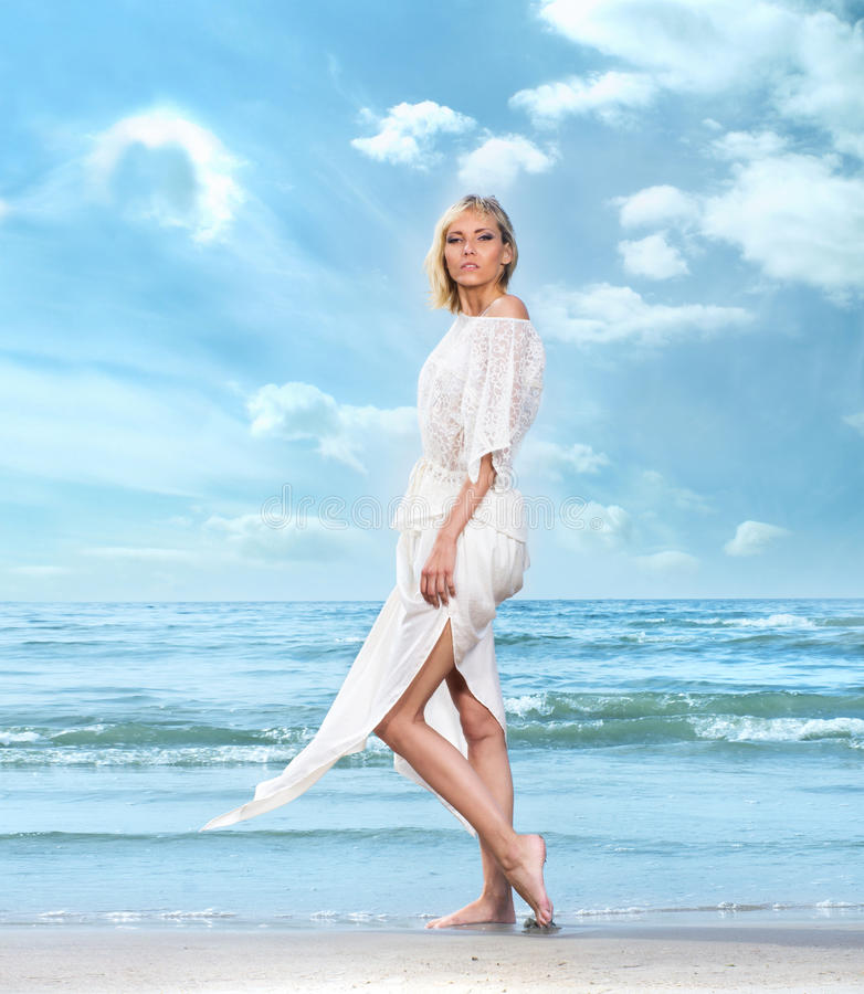 A young woman in a white dress on a beach background. A young and attractive blond Caucasian woman in a white dress on the beach. The image is taken on a sky and stock images